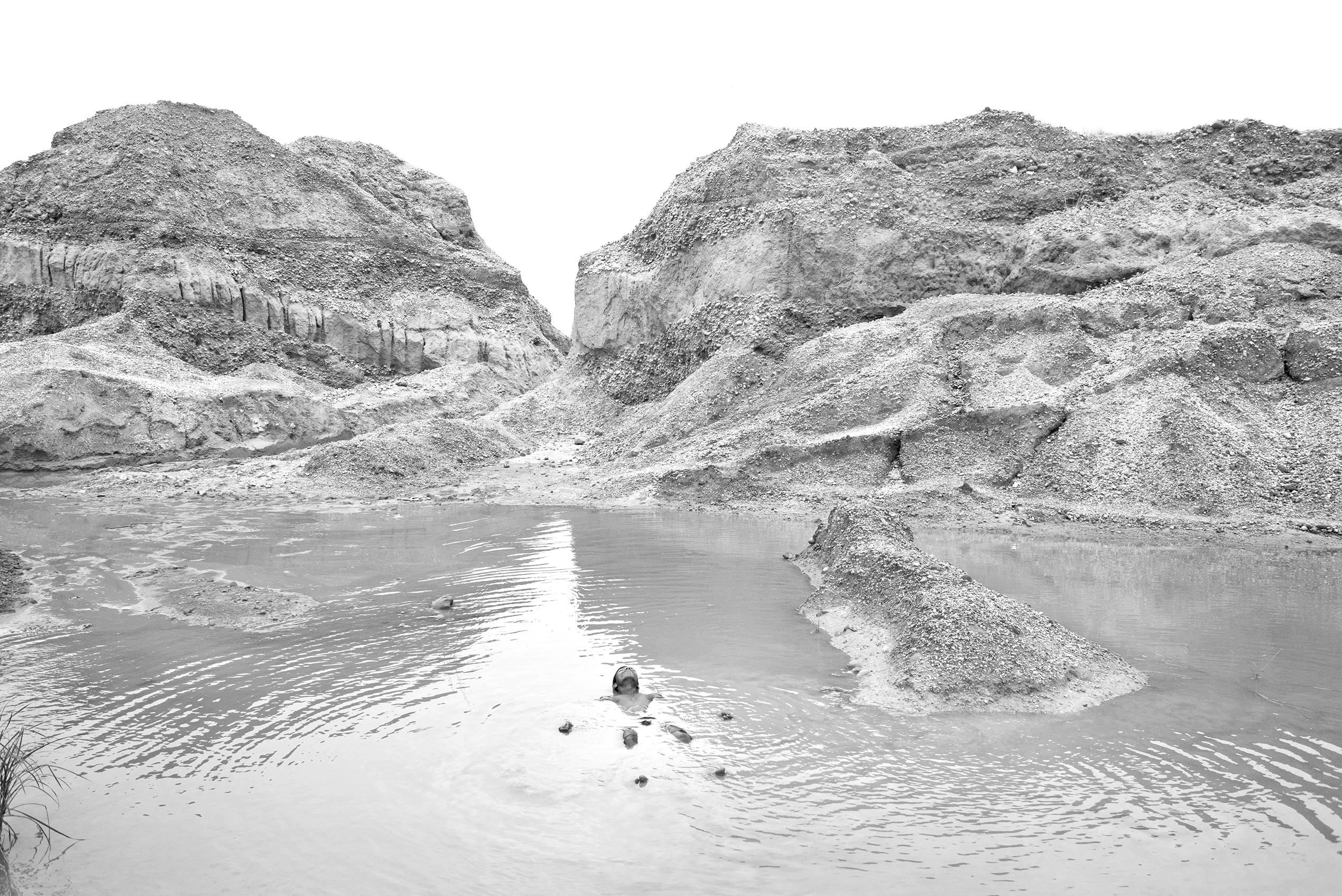Black & white photograph of a man floating in a creek, an archival pigment print by artist Munem Wasif, entitled Land of Undefined Territory