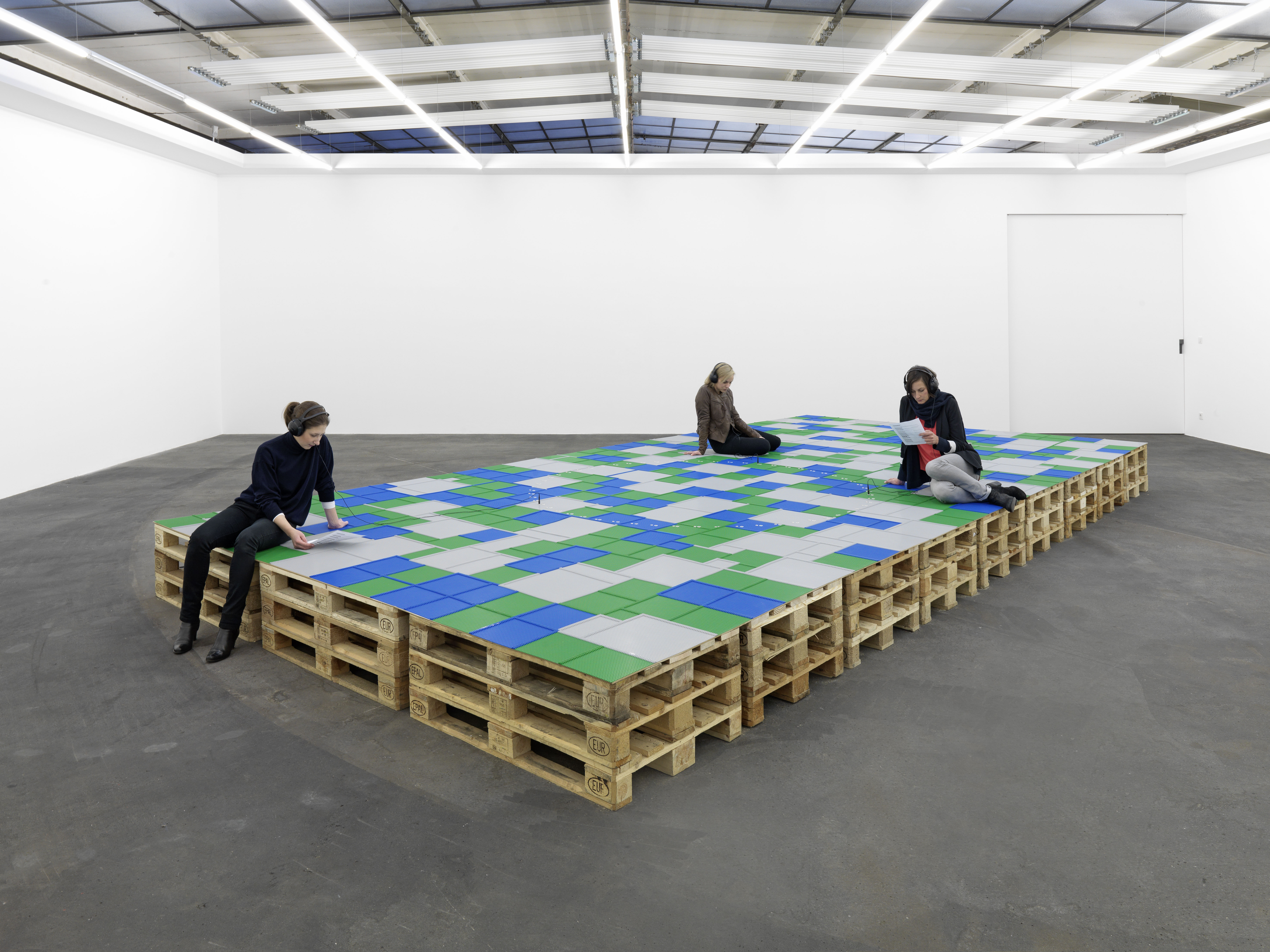 A couple of people sitting on a large mixed-media installation by Natascha Sadr Haghighian with blue, green and white-coloured Lego blocks covering wooden pallets that is stacked in the middle of a white-walled room