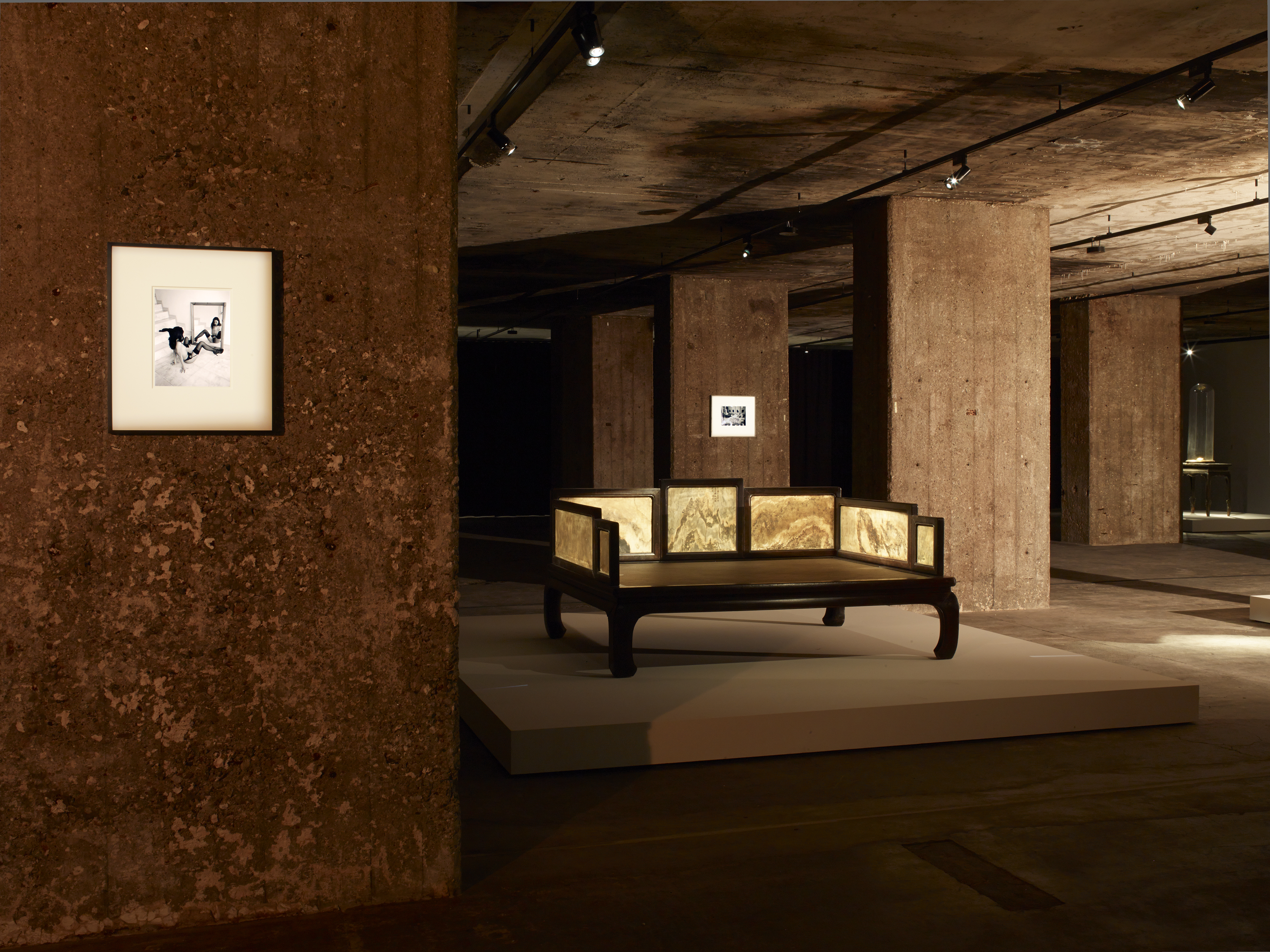 Image: Exhibition view of The Feuerle Collection, Lohan Bed, Qing Dynasty, 17 Jichi wood. Approx. 149 x 204 x 100cm. In the background works by Nobuyoshi Araki. Photo: Nic Tenwiggenhorn / VG Bild-Kunst, Bonn. © The Feuerle Collection.